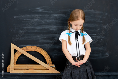 Sad child standing next to the blackboard, education problem concept Canvas Print