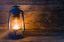 A Kerosene Lamp On The Old Wooden Background