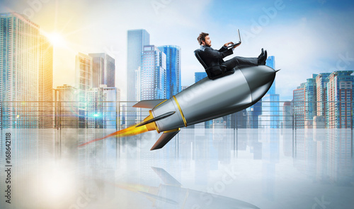 Fototapeta Fast internet concept with a businessman with laptop over a rocket obraz