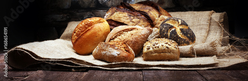 Poster Bakkerij Different kinds of bread and bread rolls on wooden table