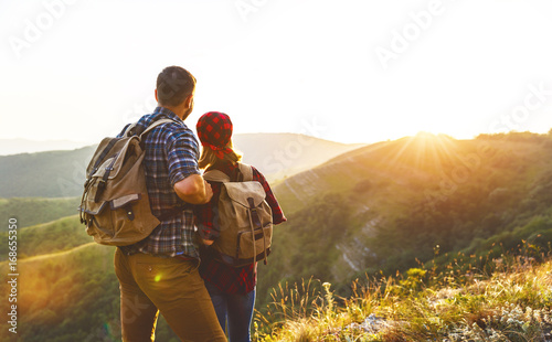 Obraz happy couple man and woman tourist at top of mountain at sunset   a hike in summer - fototapety do salonu