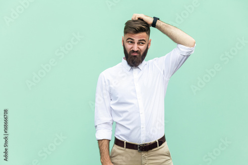 Obraz Not sure. Young adult businessman have a doubt. Studio shot - fototapety do salonu