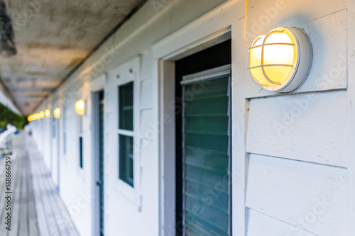 Row of hotel or motel doors outside with illuminated lights l&s in evening & Row of hotel or motel doors outside with illuminated lights lamps in ...