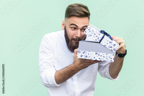 Fotografija  Cant stand, Its my! Curiosity young adult bearded man looking in gift box
