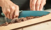 Woman Hands Chopping Chocolate...