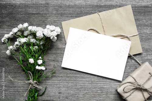 Fotografie, Obraz  blank white greeting card with white flowers bouquet and envelope with gift box