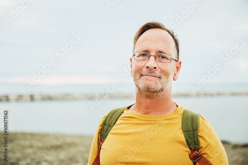 Photo  Handsome man on summer vacation by the sea, wearing yellow safran t-shirt and ba
