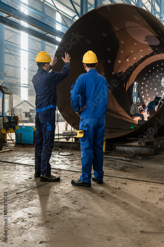 Papiers peints Tunnel Two experienced workers supervising the manufacture of a metallic cylinder in the interior of a factory