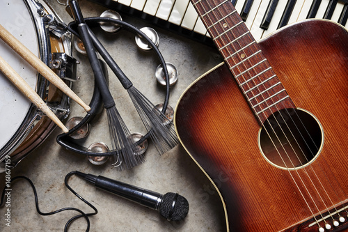 a group of musical instruments including a guitar, drum, keyboard, tambourine. - 168677159