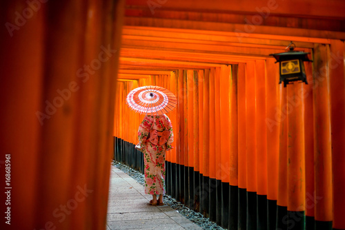 Japanese girl in Yukata with red umbrella at Fushimi Inari Shrine