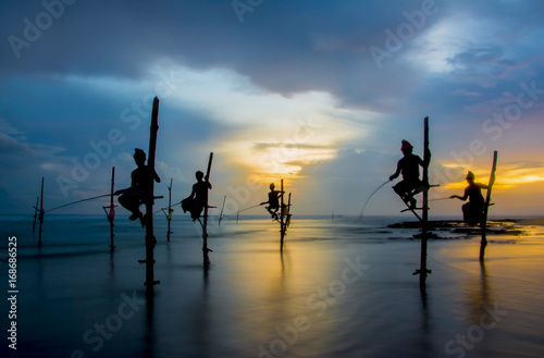 Canvas Print Silhouettes of the traditional Sri Lankan stilt fishermen on a stormy in Koggala, Sri Lanka