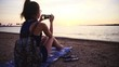 Dolly slide around person at beach take photo of sunset 4K