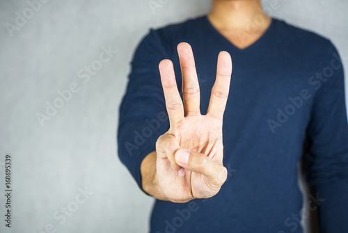 Photo  three finger salute hand gesture, on light grey background