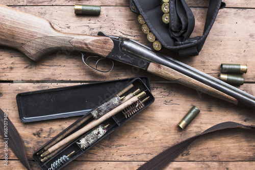 Rifle with cleaning supplies on rustic wooden background
