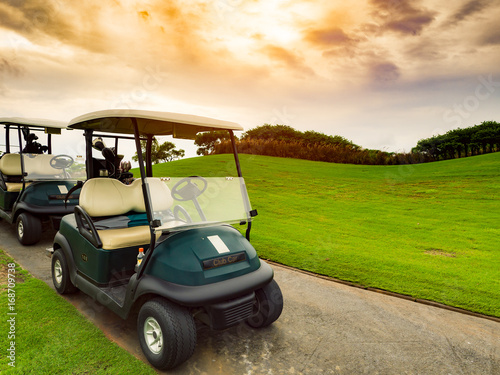Fotografie, Obraz  Golf carts or golf club cars on foot path in a green golf course fairway with be