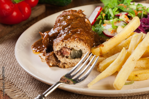 Fototapeta Pork roulade with french fries with salad
