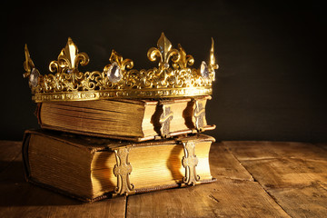 low key of beautiful queen/king crown on old books. vintage filtered. fantasy medieval period