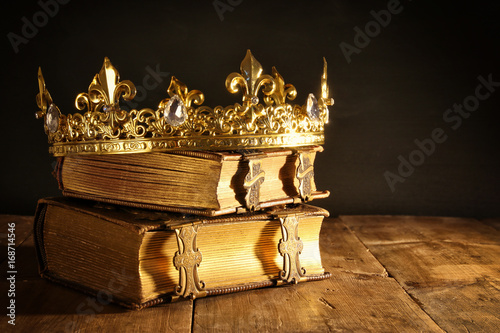 Obraz low key of beautiful queen/king crown on old books. vintage filtered. fantasy medieval period - fototapety do salonu
