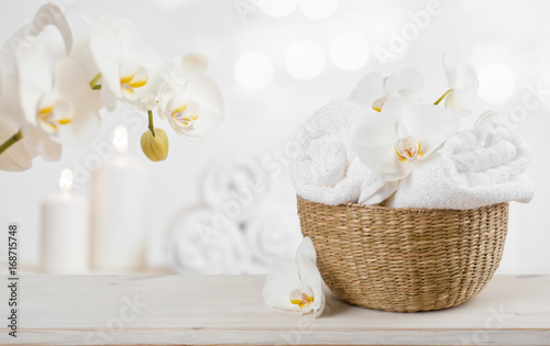 Poster Spa Wicker basket with spa towels on table over abstract background