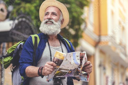 Joyful senior male traveler enjoying walk in town