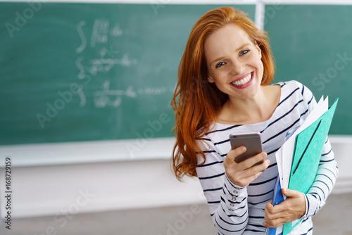 Vászonkép lachende lehrerin mit handy in der schule