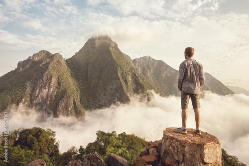 Fotografie, Obraz  Mann blickt auf Bergpanorama über den Wolken