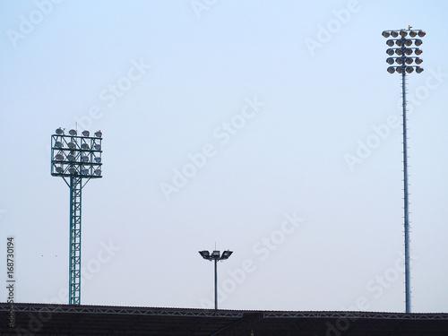 Foto op Canvas Licht, schaduw Large outdoor halogen spotlight lamp at stadium with blue sky background,