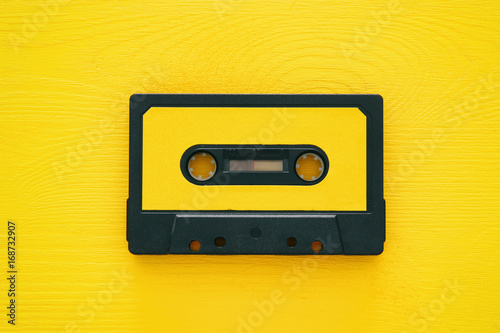 Fotografering Retro cassette tape over yellow wooden table. top view.