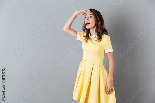 Pretty young girl in dress standing and looking far away
