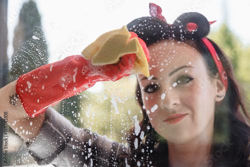 Fotografia  bella ragazza pulisce vetri della finestra di casa