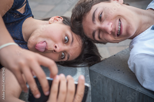 Fotografie, Obraz  frère et soeur faisant un selfie avec la langue en extérieur