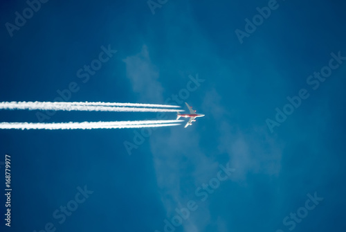Fototapeta  Silhouette of plane flying against the blue sky