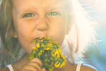 Child Of A Little Girl With Big Beautiful Eyes Sniffing Flowers And Wrinkling A Nose