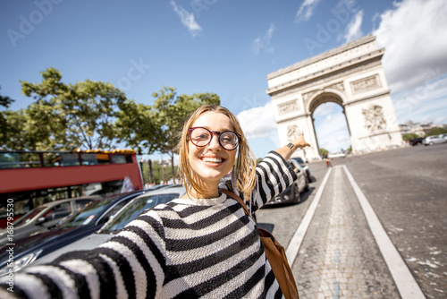 Foto  Young woman tourist making selfie portrait with famous Triumphal Arch on the bac