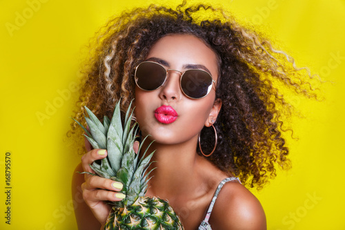 Fashion portrait afro american girl in sunglasses and pineapple over yellow background