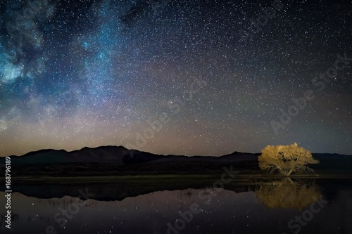 Starry night sky reflected in water, silhouetted mountains, and glowing golden t Fototapeta