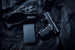 Gun, mobile phone and leather jacket on black background, criminality concept