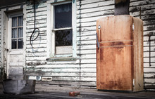 Horizontal Image Of A Very Old Rusted Fridge Sitting Outside On The Veranda Of An Old White Abandoned House In The Summer Time.