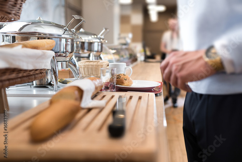 Businessman in front of the hotel buffet taking a breakfast