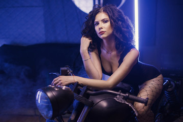 Fototapeta na wymiar Curly biker girl in black lingerie sitting on old fashioned motorcycle in interior on blue lights background