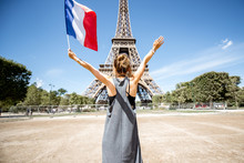 Young Woman Tourist Standing Back With French Flag Enjoying View On The Eiffel Tower In Paris