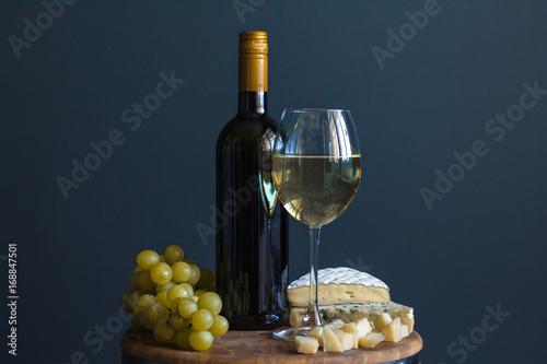 butelka-i-szklo-z-bialym-winem-w-towarzystwie-winogron-i-sera-camembert