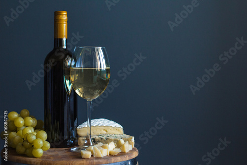 Photo  Bottle and glass with white wine near cheese composition on a wooden board