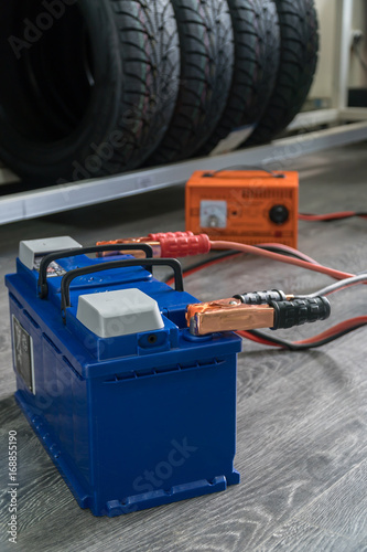 Recharging The Car Battery On A Wooden Background
