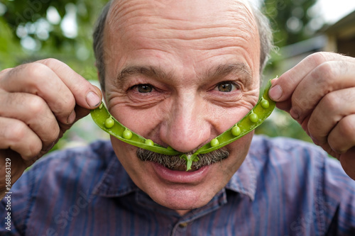 Fotografie, Obraz  An elderly man is fooling around