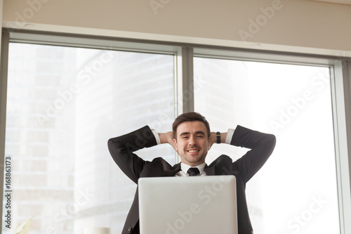 Relaxed Happy Businessman Sitting With Hands Behind Head At