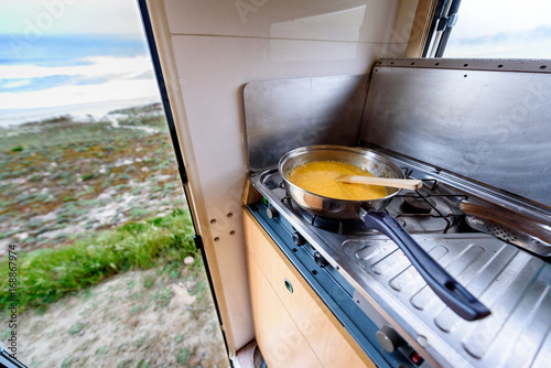 Photo  Cooking dinner or breakfast in camper motorhome with beach view.