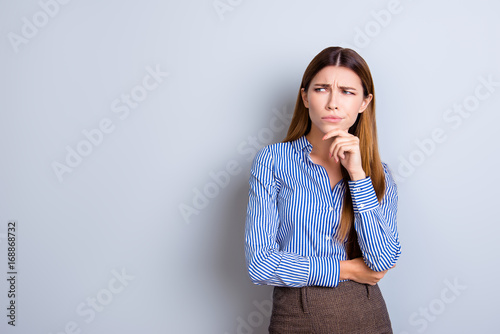 Sceptical young business lady is unsure what to do. She has focused grimace, wearing strict formal wear, standing on pure light background