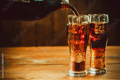 Poster Sap Pouring beautiful cold drink of Cola with ice cubes with a boiler straws in glasses on wooden background with free space