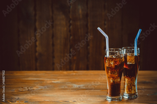 Fototapeta Beautiful cold drink of Cola with ice cubes with a boiler straws in glasses on wooden background with free space